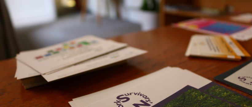 Photograph of leaflet with Survivors' Network logo at the top (logo comprises of the organisation name in purple) - the background is blurred but shows other leaflets and a chair at a table