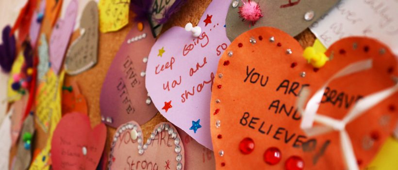 Cut out paper hearts with positive messages on. Visible include 'you are brave and believed' and 'keep going...you are so strong'