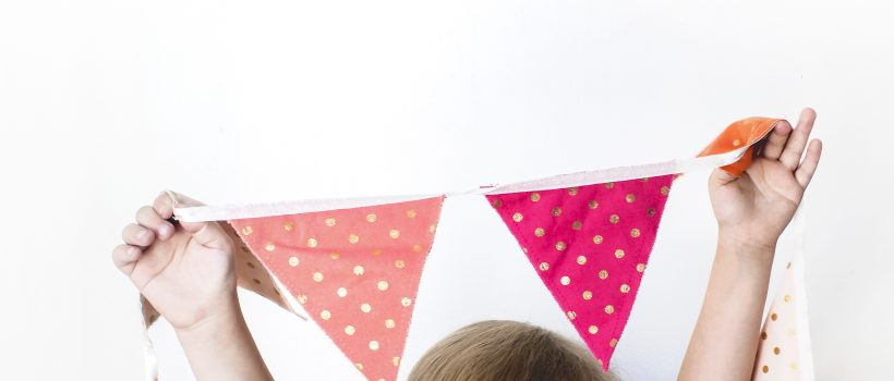 white girl hanging spotty bunting, photo taken from behind and shows the top of her head and arms holding up the bunting