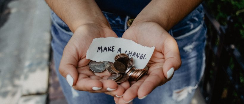 "person holds coins and a note that says ""make a change"" in their upturned palms"