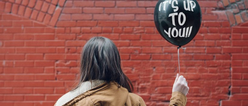 "woman turned away from camera holding balloon with ""its up to you"" written on it"