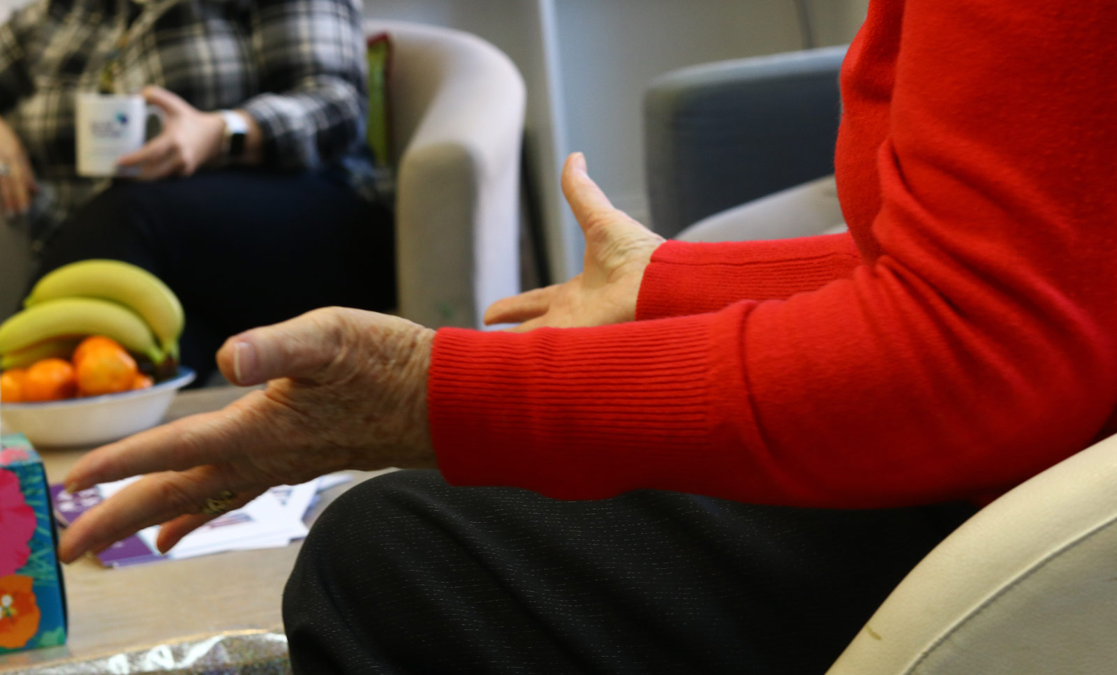A woman in counselling in a red sweater gesticulating with hands