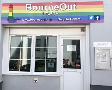 Photo of front of building, with rainbow sign that says BourneOut LGBT+, Drop In Centre www.bourneout.org. The doors are white and there is a double window to the left of the door.