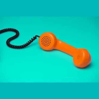 Orange old fashioned phone handset on a blue background