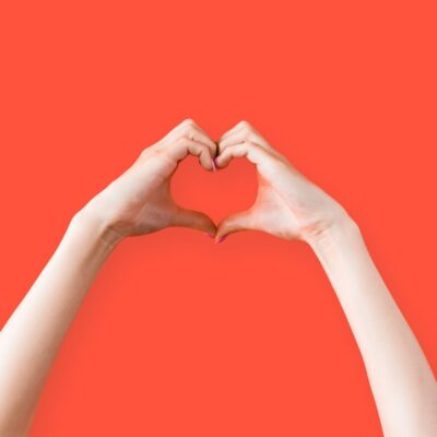 Photo of a white person reaching up over an orange background to make a heart with their two hands - only their arms and hands are visible.